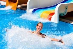 Niño en el tobogán acuático en aquapark Fotografía de archivo