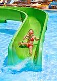 Niño en el tobogán acuático en el aquapark. imagen de archivo