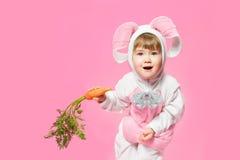 Niño en el traje de las liebres del conejito que sostiene zanahorias. Imagen de archivo libre de regalías