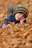 Niño en hojas de otoño Fotos de archivo libres de regalías