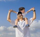 Niño en hombros del hombre Imagen de archivo