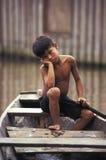 Niño en la canoa en el Amazonas, el Brasil Fotos de archivo