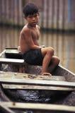 Niño en la canoa en el Amazonas, el Brasil imagen de archivo
