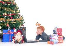 Niño en la computadora portátil, Navidad tres Imagenes de archivo