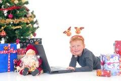 Niño en la computadora portátil, Navidad tres Fotografía de archivo libre de regalías