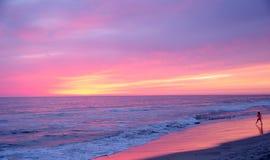 Niño en la costa con puesta del sol espectacular fotografía de archivo