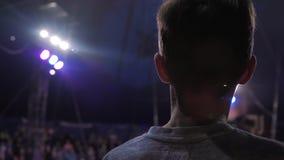 Niño en la demostración mágica que disfruta del truco peligroso del gimnasta en el aire metrajes