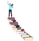 Niño en la escalera de libros Fotos de archivo