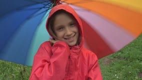 Niño en la lluvia, el jugar del niño al aire libre en paraguas de giro de la muchacha del parque en llover día imagen de archivo