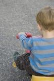 Niño en la opinión de la parte posterior del triciclo Imagen de archivo