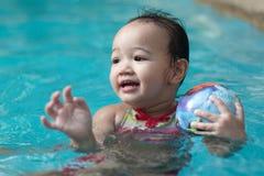 Niño en la piscina con una bola Fotos de archivo libres de regalías