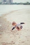 Niño en la playa que juega conchas marinas de la cosecha Imagen de archivo