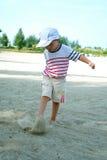 Niño en la playa que juega la arena Foto de archivo