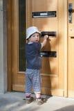 Niño en la puerta con el letterbox fotografía de archivo