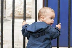 Niño en la puerta del hierro Fotografía de archivo libre de regalías