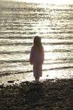 Niño en la puesta del sol Fotos de archivo