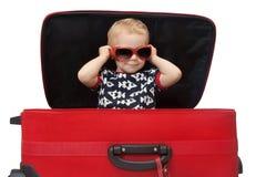 Niño en las gafas de sol que miran hacia fuera la maleta roja Foto de archivo libre de regalías
