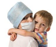 Niño en las manos en el doctor Fotos de archivo