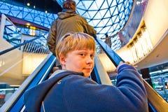 Niño en miradas de la escalera móvil Fotos de archivo