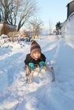 Niño en nieve del invierno del trineo o del trineo Imagenes de archivo