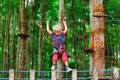 Niño en obstáculo del paso del arnés de seguridad en parque de la cuerda de la aventura imágenes de archivo libres de regalías