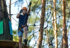 Niño en parque de la aventura del bosque Niño en casco anaranjado y subidas azules de la camiseta en alto rastro de la cuerda foto de archivo