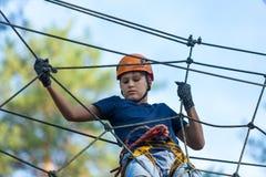 Niño en parque de la aventura del bosque Niño en casco anaranjado y subidas azules de la camiseta en alto rastro de la cuerda imagen de archivo