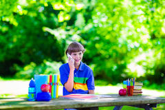 Niño en patio de escuela que estudia y que habla en el teléfono Fotos de archivo
