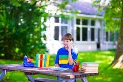Niño en patio de escuela que estudia y que habla en el teléfono Foto de archivo libre de regalías