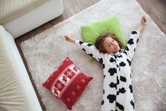 Niño en pijamas de la impresión de la vaca Foto de archivo