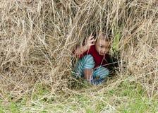 Niño en pila del heno Imagen de archivo libre de regalías