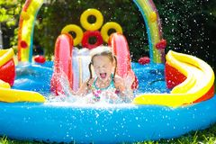 Niño en piscina del jardín con la diapositiva Fotos de archivo