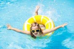 Niño en piscina en el juguete del anillo Nadada de los ni?os imagen de archivo