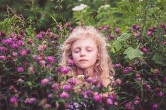 Niño en prado floral Imagenes de archivo