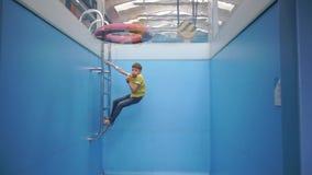 Niño en ropa en una piscina seca metrajes