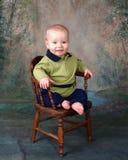 Niño en silla de madera Fotos de archivo