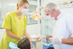 Niño en silla dental con el dentista después de reparar los dientes foto de archivo