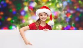 Niño en sombrero del ayudante de santa con el tablero blanco en blanco Imágenes de archivo libres de regalías
