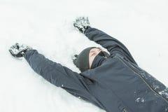 Niño en sombrero y capa que coloca en nieve Fotografía de archivo libre de regalías