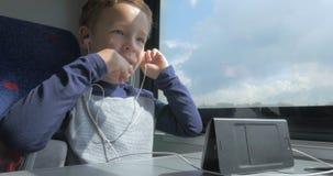 Niño en tren que habla en móvil usando las manos fijadas libremente metrajes