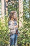 Niño en un alza en el bosque que come el pan frito en el fuego Foto de archivo libre de regalías