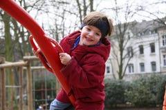 Niño en un balancín (c) Fotografía de archivo libre de regalías