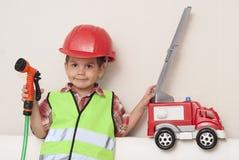 Niño en un casco rojo y con un coche de bomberos imagenes de archivo