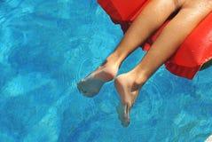 Niño en un colchón inflable rojo en piscina Imagen de archivo libre de regalías
