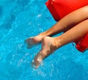 Niño en un colchón inflable rojo en piscina Fotografía de archivo libre de regalías