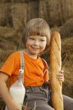 Niño en un pajar con leche del pan Imágenes de archivo libres de regalías