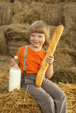 Niño en un pajar con pan Imagenes de archivo