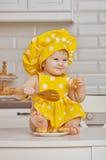 Niño en un traje amarillo del cocinero en los guisantes blancos Imágenes de archivo libres de regalías