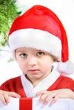 Niño en un traje de Papá Noel con un presente. Imagenes de archivo