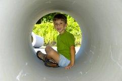 Niño en un tubo Foto de archivo libre de regalías